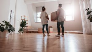 A couple in a near empty room, holding moving boxes after moving into their new home