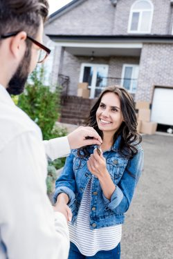 A woman in a jean jacket standing in front of a house, shaking hands with a realtor and being handed keys